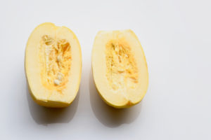 Fresh spaghetti squash cut in half on white background
